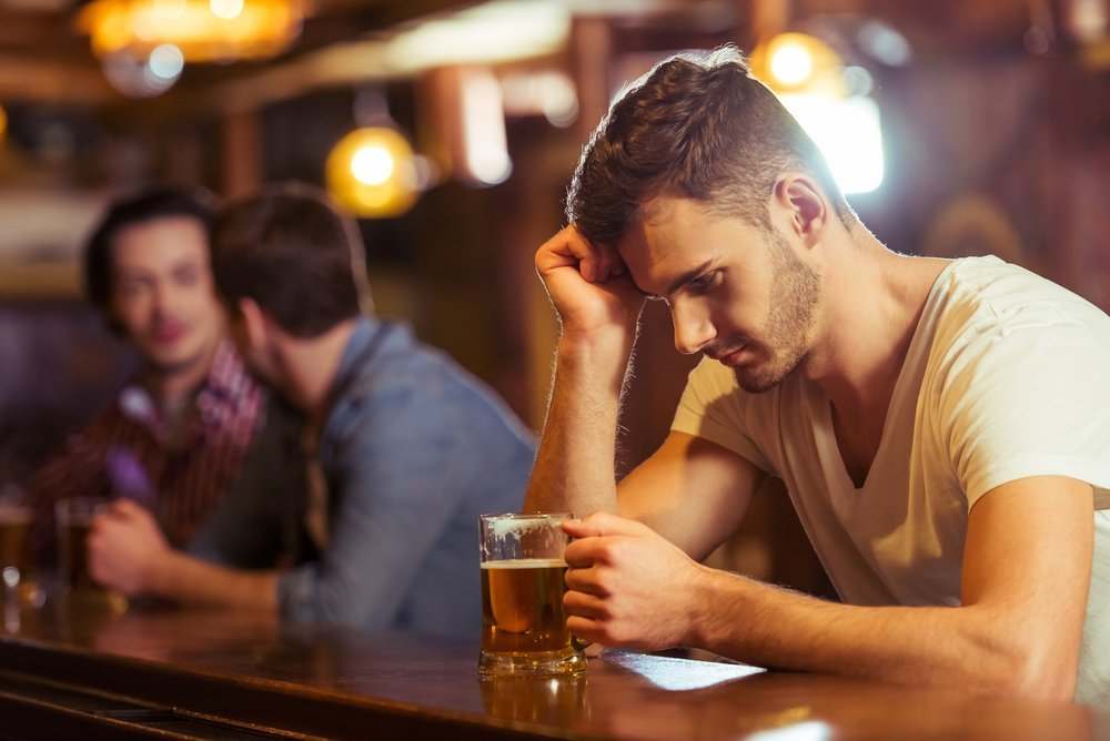 Young man in white t-shirt is looking at glass of beer while sitting at bar counter in pub | Photo: Shutterstock