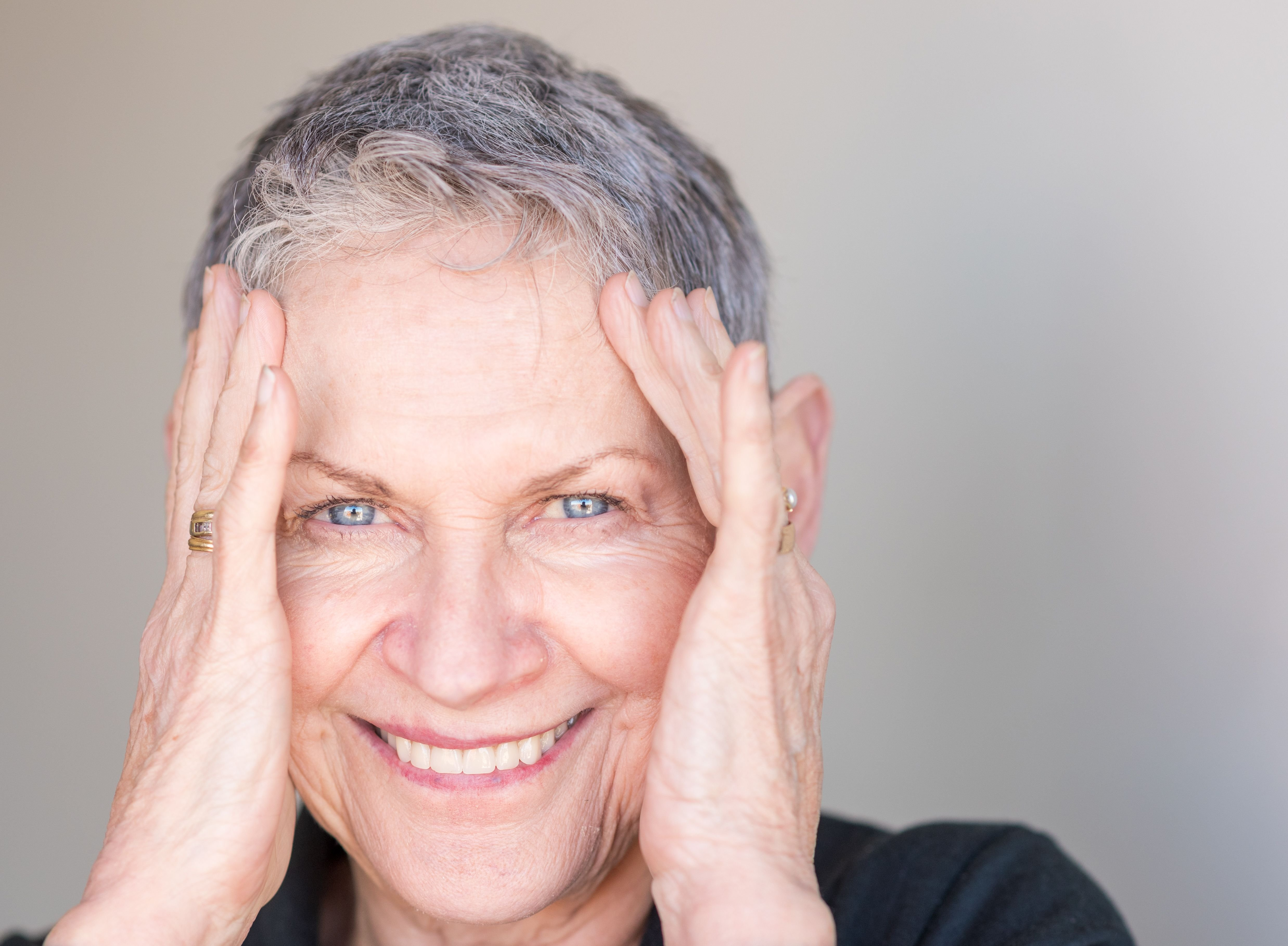 Close up portrait of beautiful older woman with short grey hair smiling with hands around face. | Source: Shutterstock