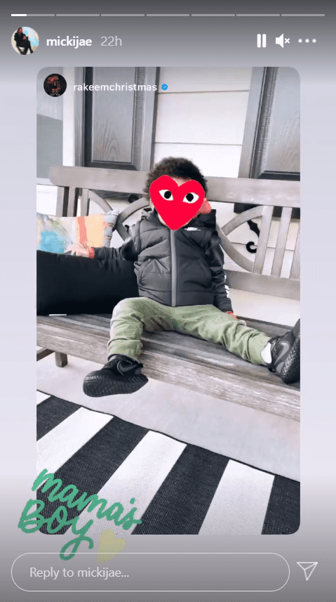 A picture of Jasmine Jordan's son, Rakeem, seated on a bench with his face covered with a red heart emoji and accompanied with a caption | Photo: Instagram/mickijae