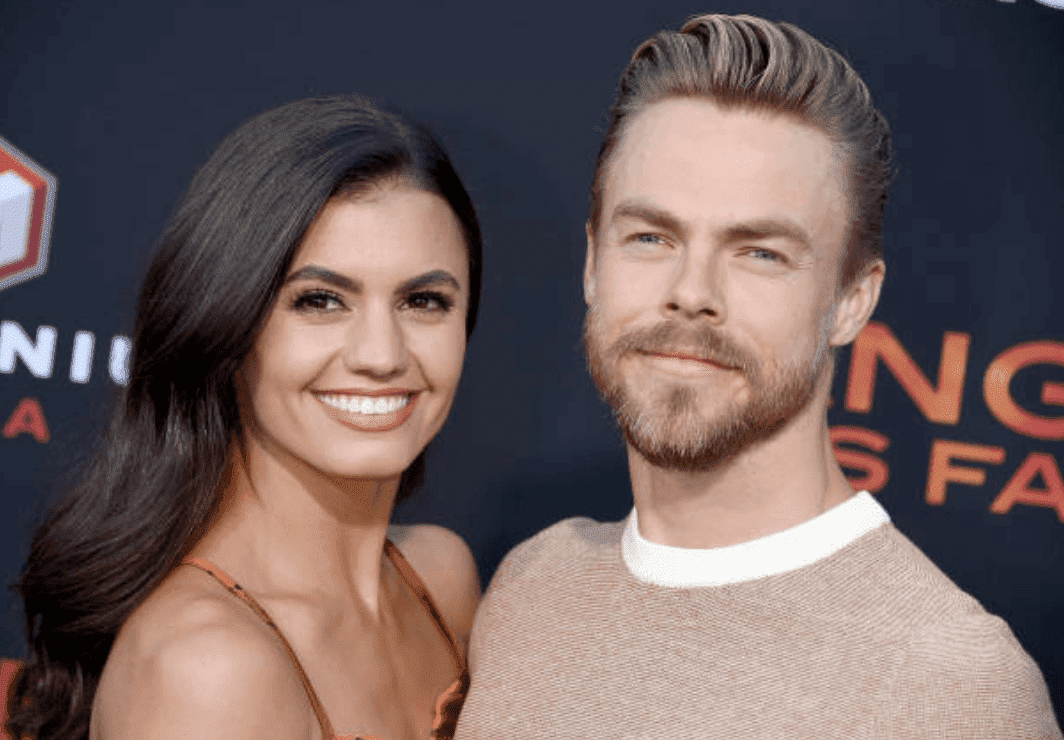 """Derek Hough and his girlfriend, Hayley Erbert pose on the red carpet as they arrive at the  """"Angel Has Fallen"""" premiere, on August 20, 2019, in Westwood, California 