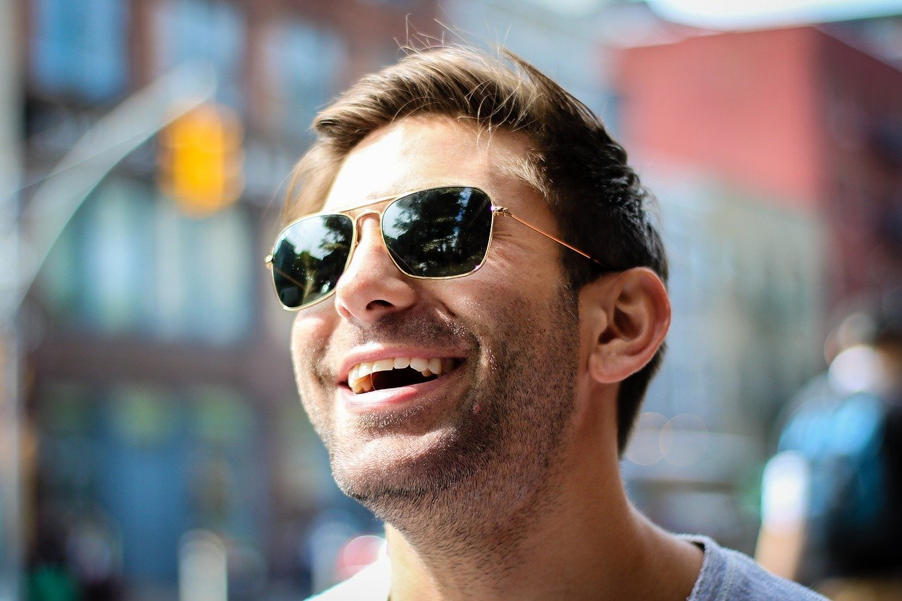 A man wearing sunglasses and laughing while outdoors   Photo: Pixabay/Pexels
