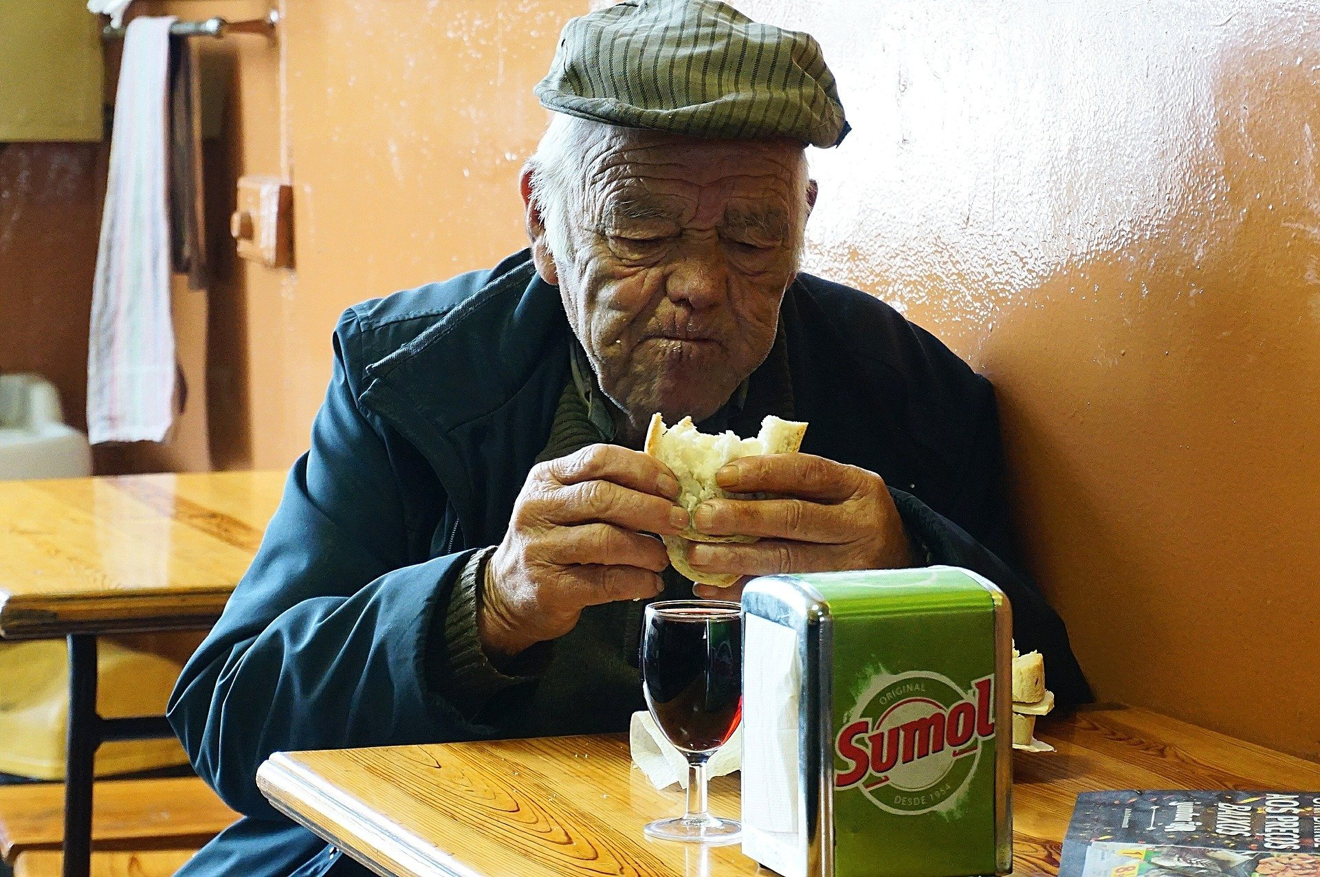 An old man sitting and eating a meal at a restaurant   Photo: Pixabay/Antonio Valente