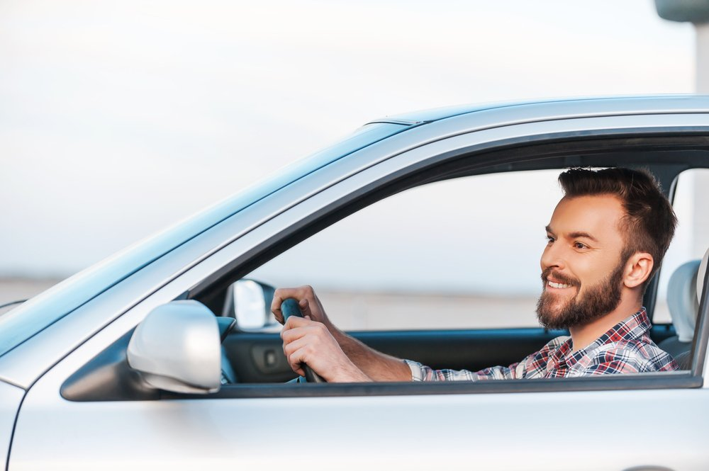 A photo of a young man driving his car and smiling. | Photo: Shutterstock
