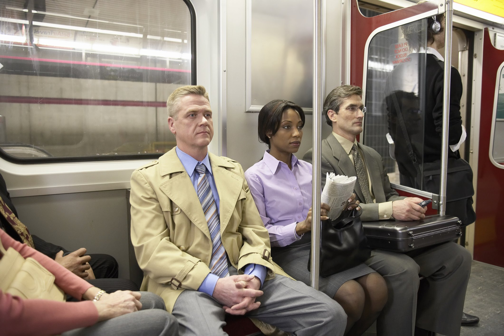 People seated side by side in a subway train.   Photo: Getty Images