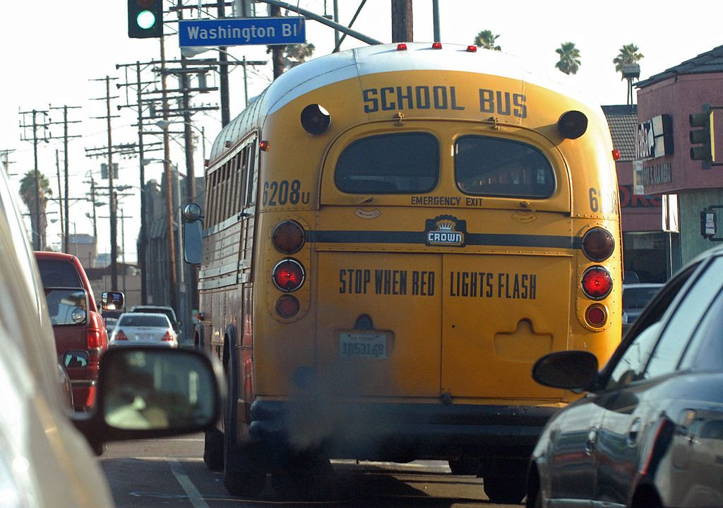 A yellow school bus driving through a busy street. | Source: Getty Images