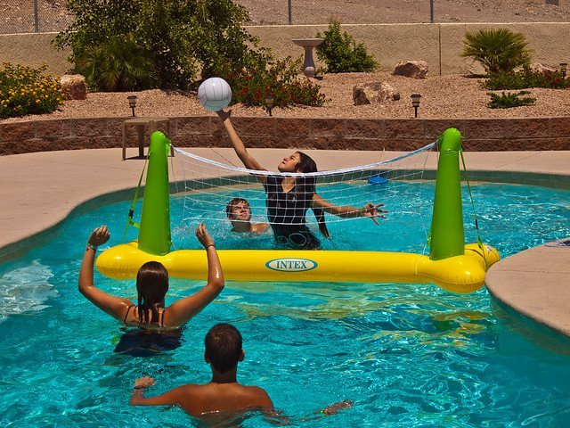 People enjoying a game of pool volleyball. | Photo: Flickr