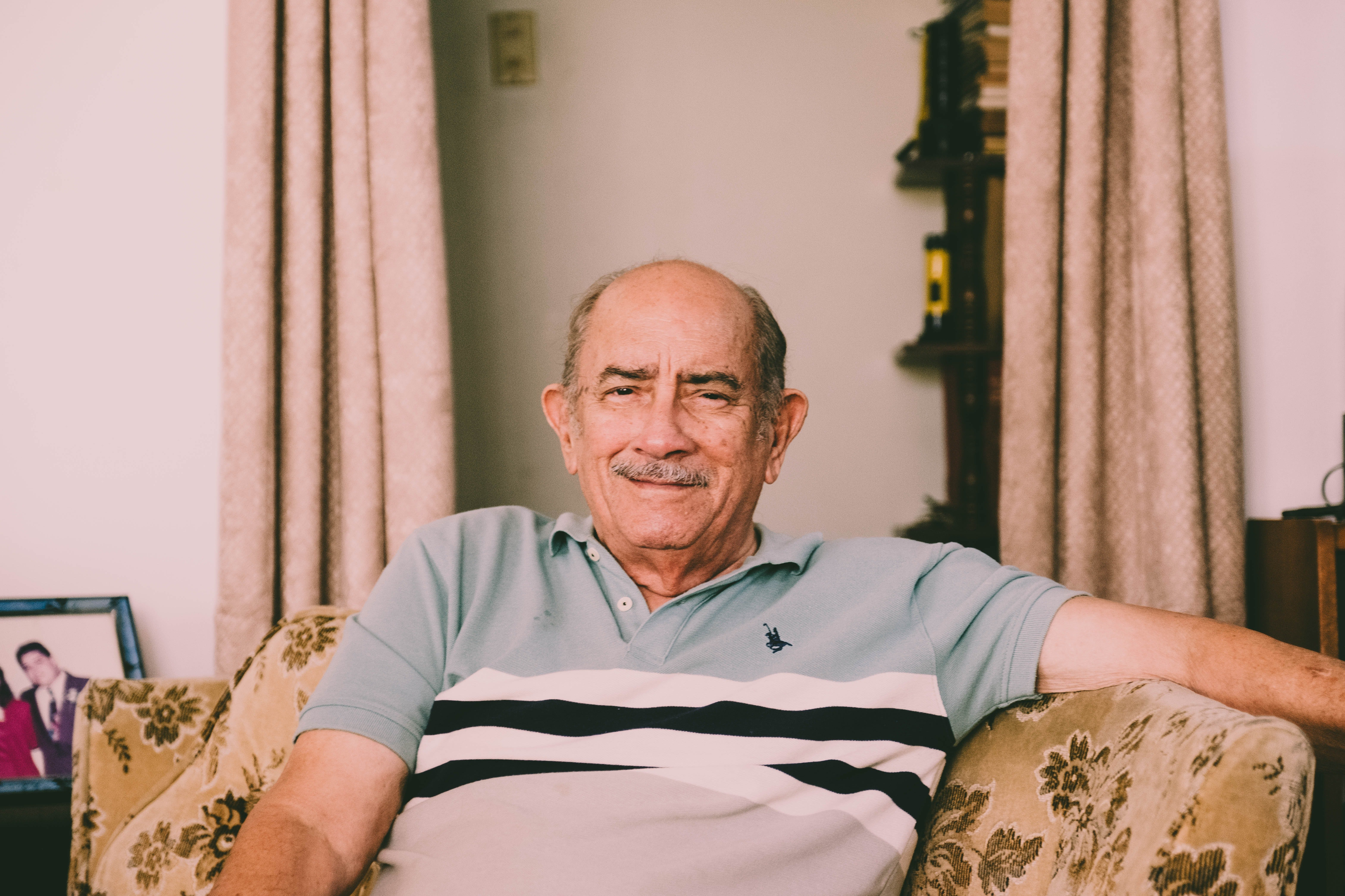 An elderly man sitting on a couch.   Photo: Pexels
