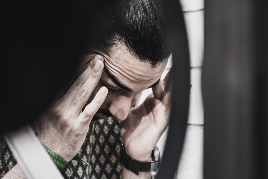A frustrated man tries to calm himself by massaging his temples | Photo: Unsplash