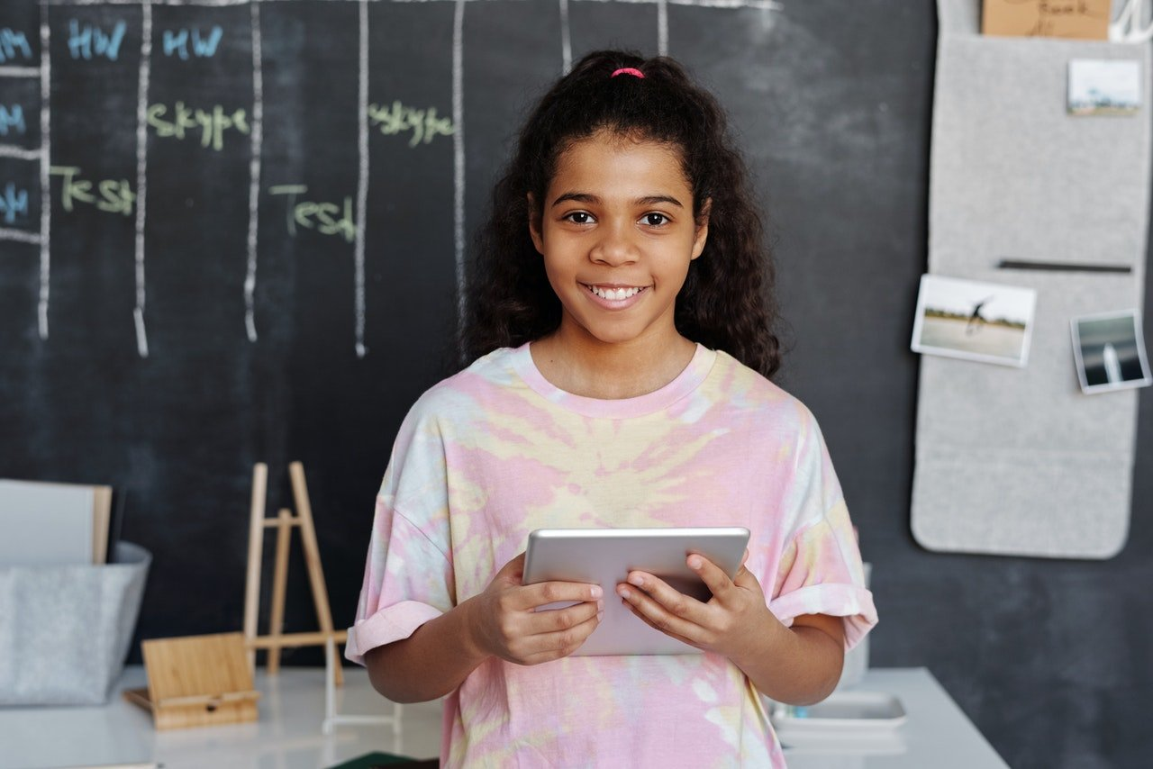 Young school girl smiling while holding a tablet | Photo: Pexels