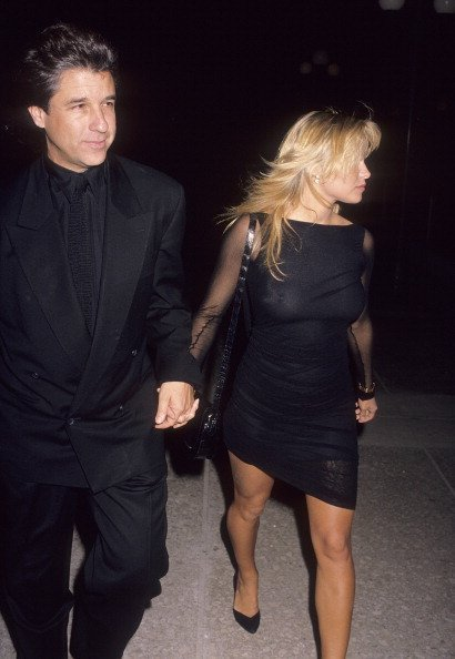 "Producer Jon Peters and actress Pamela Anderson attend the ""Glory"" Century City Premiere on December 11, 1989 at the Cineplex Odeon Century Plaza Cinemas in Century City, California 