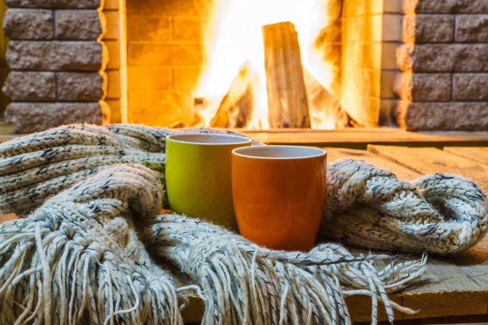 A photo of two mugs and wool scarves near cozy fireplace. | Photo: Shutterstock