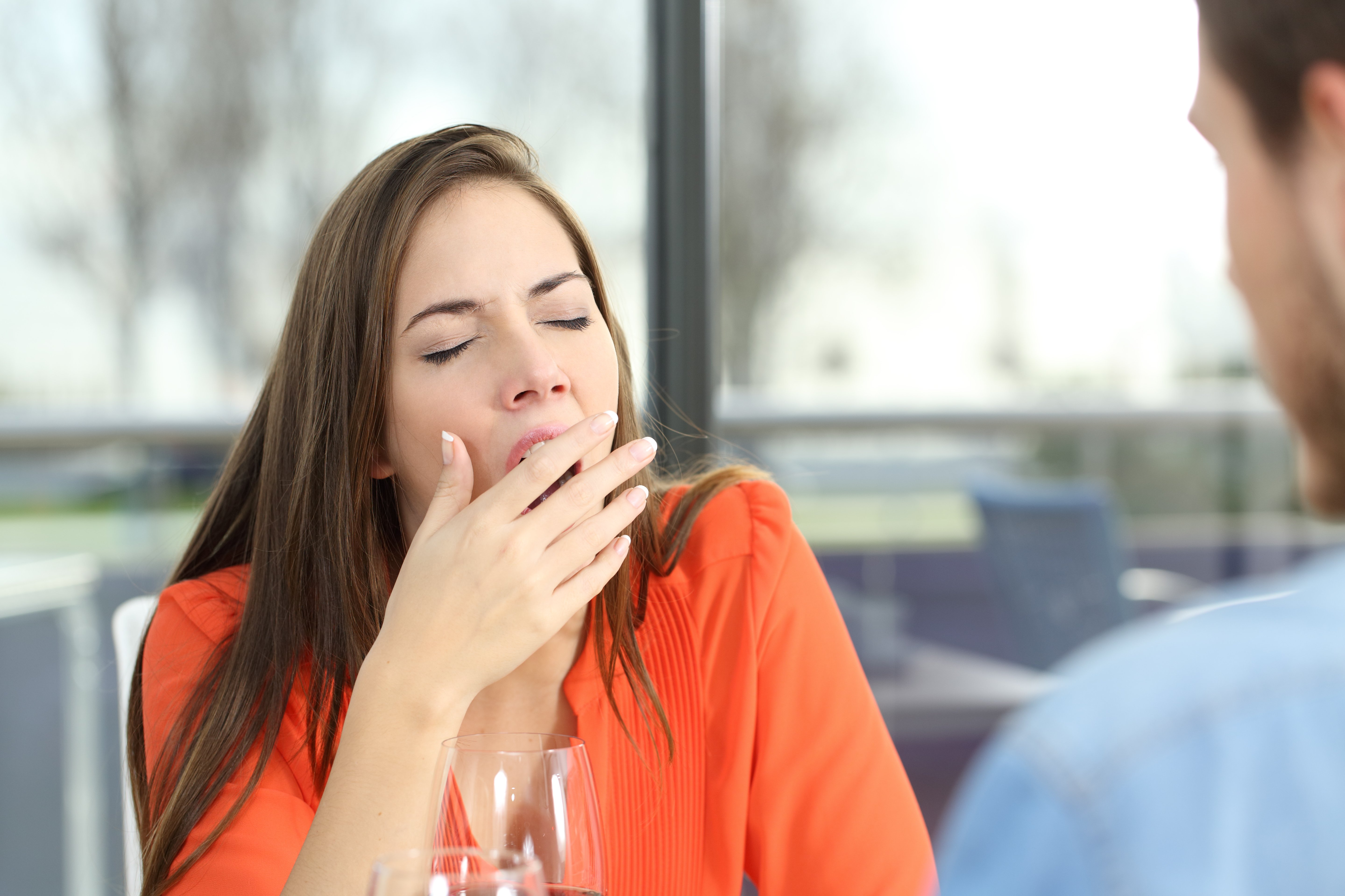 Photo of woman yawning while sitting at a table with a man. | Source: Shutterstock