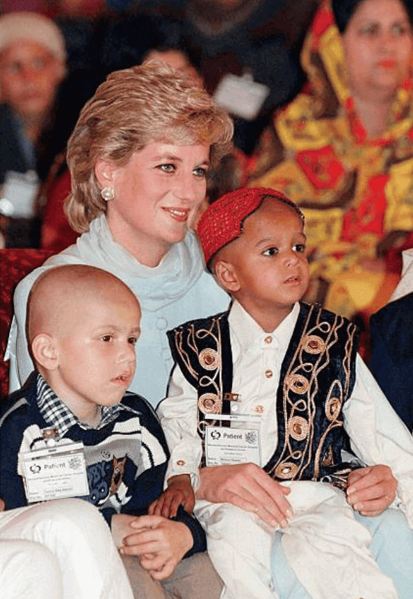 Princess Diana sits with two children on her lap at an event for the Shaukat Khanum Memorial Cancer Hospital, April 01, 1996, in Lahore, Pakistan | Source: Anwar Hussein/Getty Images