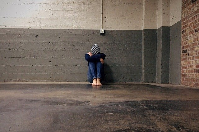 Girl sits against wall with head between knees | Photo: Pixabay