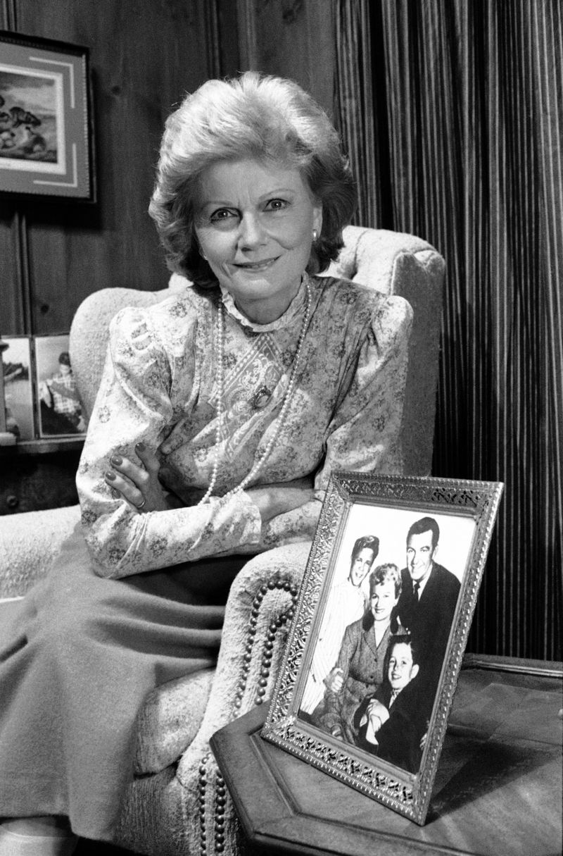 Barbara Billingsley posing with a cast photo. | Photo: Legacy.com