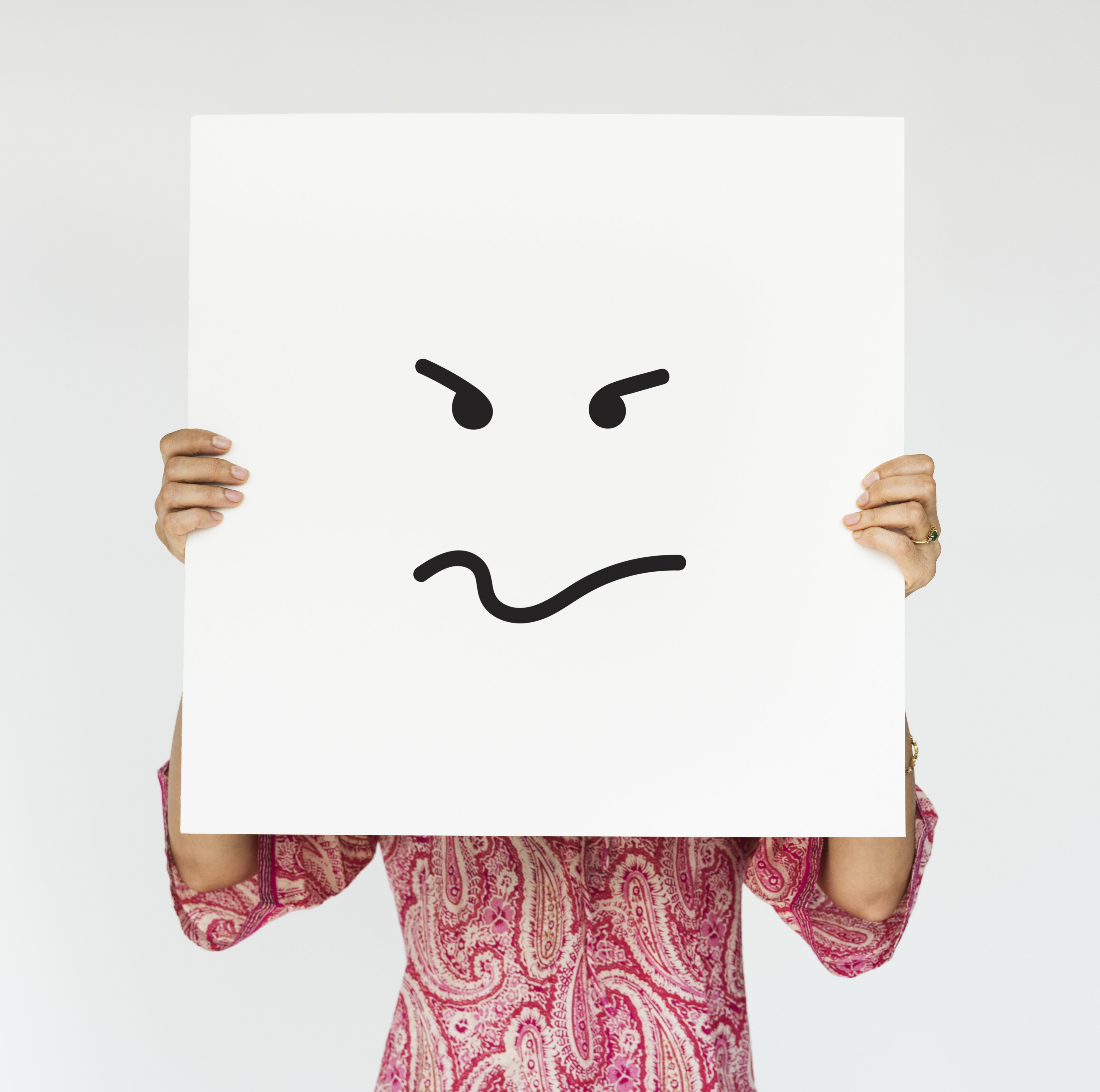 A woman holding an angry face painted on a signboard.   Source: Freepik.