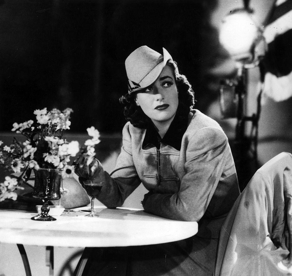La actriz de cine estadounidense Joan Crawford sentada en una mesa.  Fuente: Getty Images