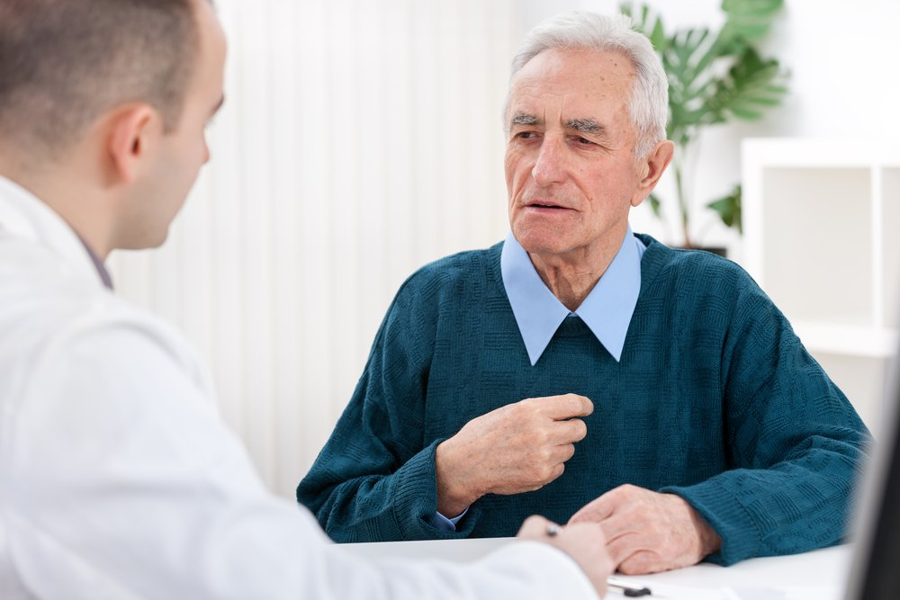 A senior man sitting and discussing with his doctor. | Photo: Shutterstock.