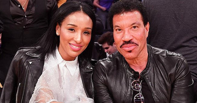 Lionel Richie's Longtime Girlfriend Strikes Cozy Pose on Pillows in a Revealing Shirt & Black Bra