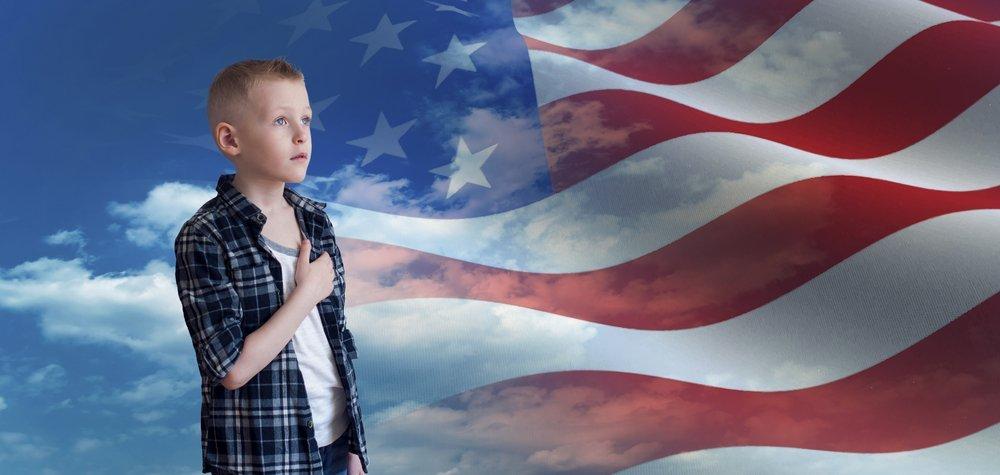 Junge mit Hand auf dem Herzen vor der Amerikanischen Flagge | Quelle: Shutterstock