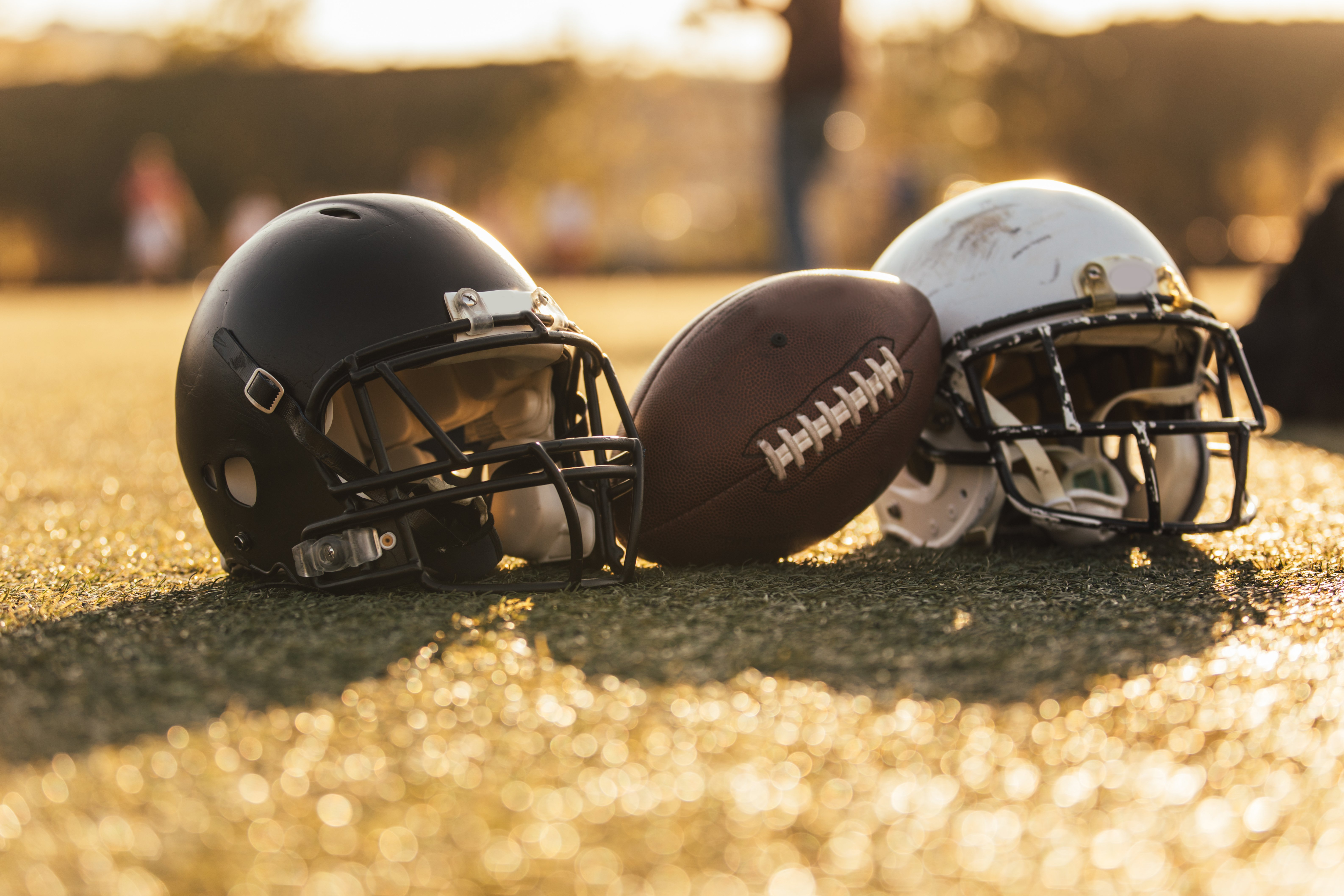 An image of an American football helmet and ball on a field. | Photo : Getty Images