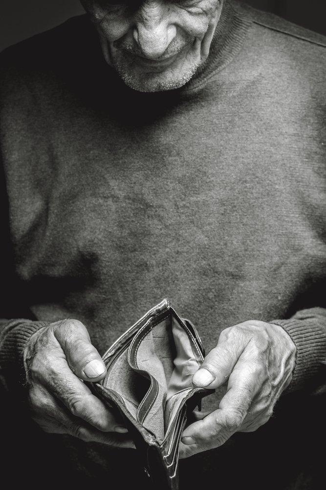 Un homme âgé tenant un portefeuille vide. | Photo: Shutterstock