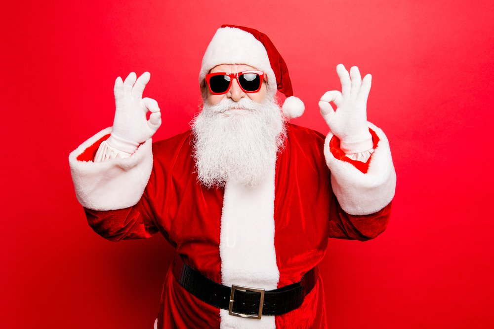 """A man dressed in a red Santa Claus costume while wearing sunglasses and flashing the """"okay"""" sign with both hands   Photo: Shutterstock/Roman Samborskyi"""