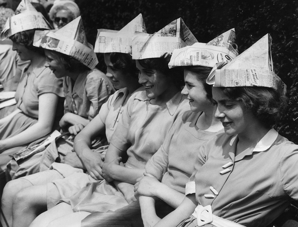 Schoolgirls wearing newspaper hats to protect them from the sun while watching Wimbledon during a heatwave   Source: Getty Images