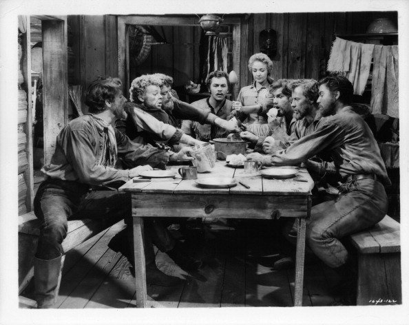 Jane Powell and Howard Keel are amazed at the free for all brawl which always occurs when the rest of the brothers gather around the table in a scene from the film 'Seven Brides For Seven Brothers', 1954 | Photo: Getty Images