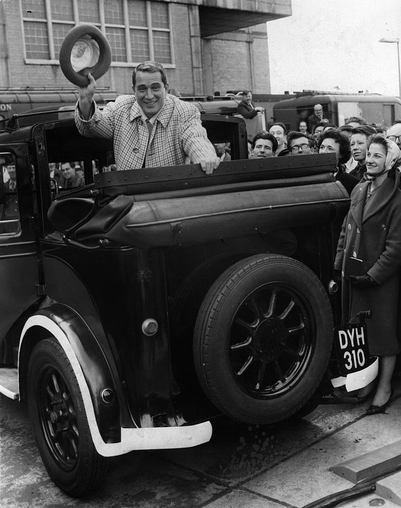 Perry Como (1912 - 2001) rides in an old taxi after his arrival at London airport. | Getty Images