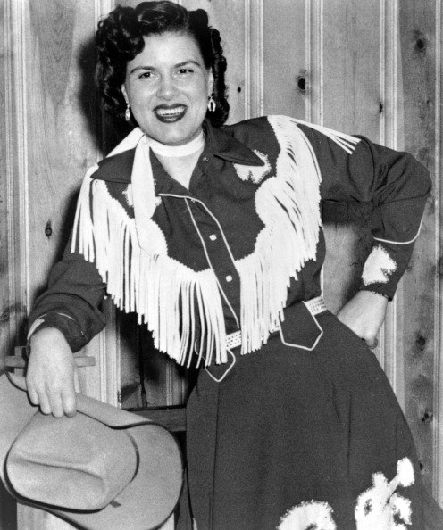 Patsy Cline plays the piano wearing a fringed dress and holding a cowboy hat in circa 1958. | Photo: Getty Images