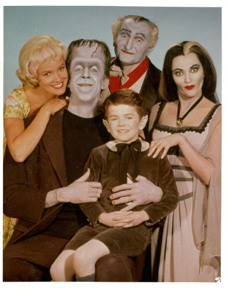 """Pat Priest, Al Lewis, Butch Patrick, Fred Gwynne, and Yvonne De Carlo in a publicity photograph from the television series """"The Munsters,"""" circa 1964. 