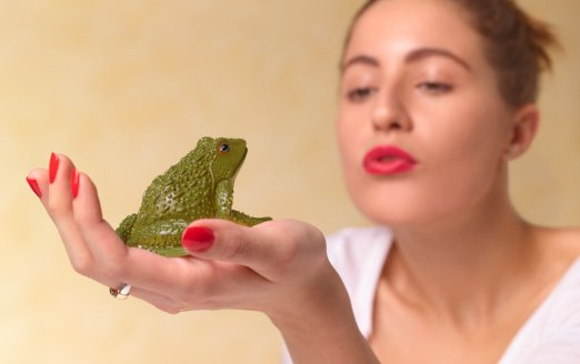 Young woman blowing a kiss to a frog. | Photo: Getty Images