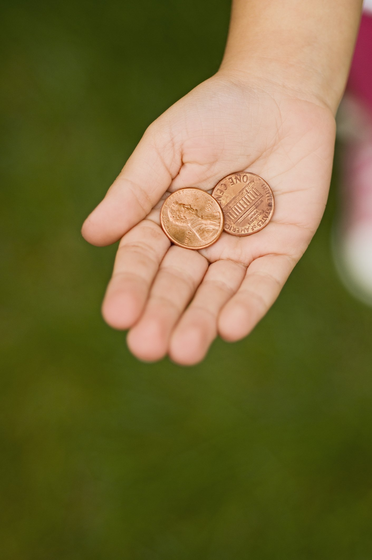 Hand holding pennies | Photo: Getty Images