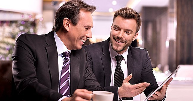 Two rich male friends talking and laughing over coffee | Photo: Getty Images
