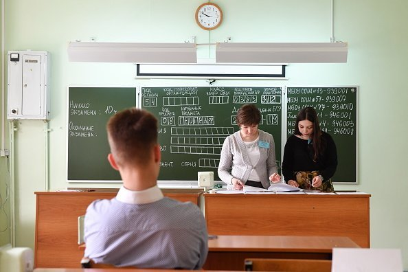 Teachers and a secondary school student  in classroom preparing for an exam | Photo: Getty Images
