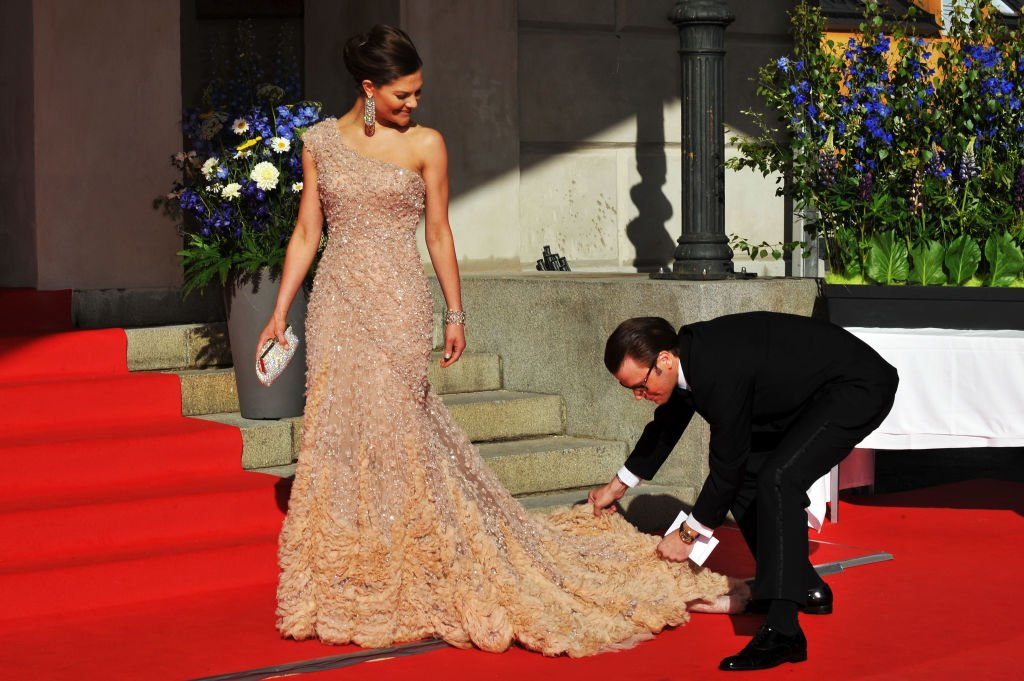 Princess Victoria is helped with her dress by fiance Daniel Westling during the Government Pre-Wedding Dinner for Crown Princess Victoria of Sweden and Daniel Westling at The Eric Ericson Hall on June 18, 2010 in Stockholm, Sweden | Photo: Getty Images