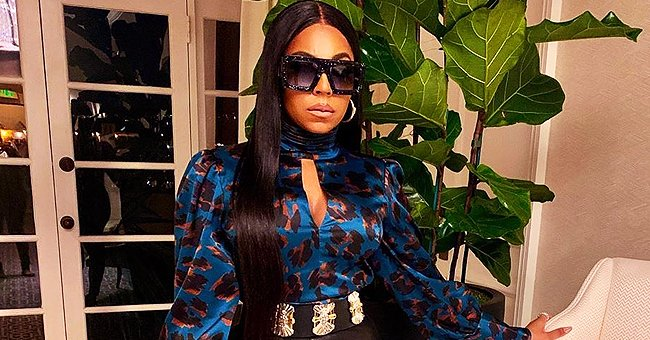 Ashanti Flaunts Curvy Figure in Black Leather Pants, One High Heel & Printed Top in New Pics