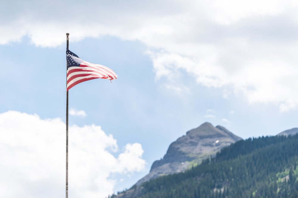 A flagpole with the American flag waving in the wind and mountain peak in summer. | Photo: Shutterstock