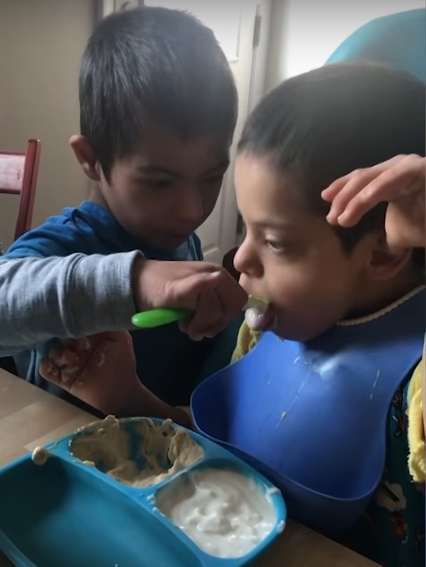Simon feeding Alex with a spoon l Source: Youtube/Carters Clips