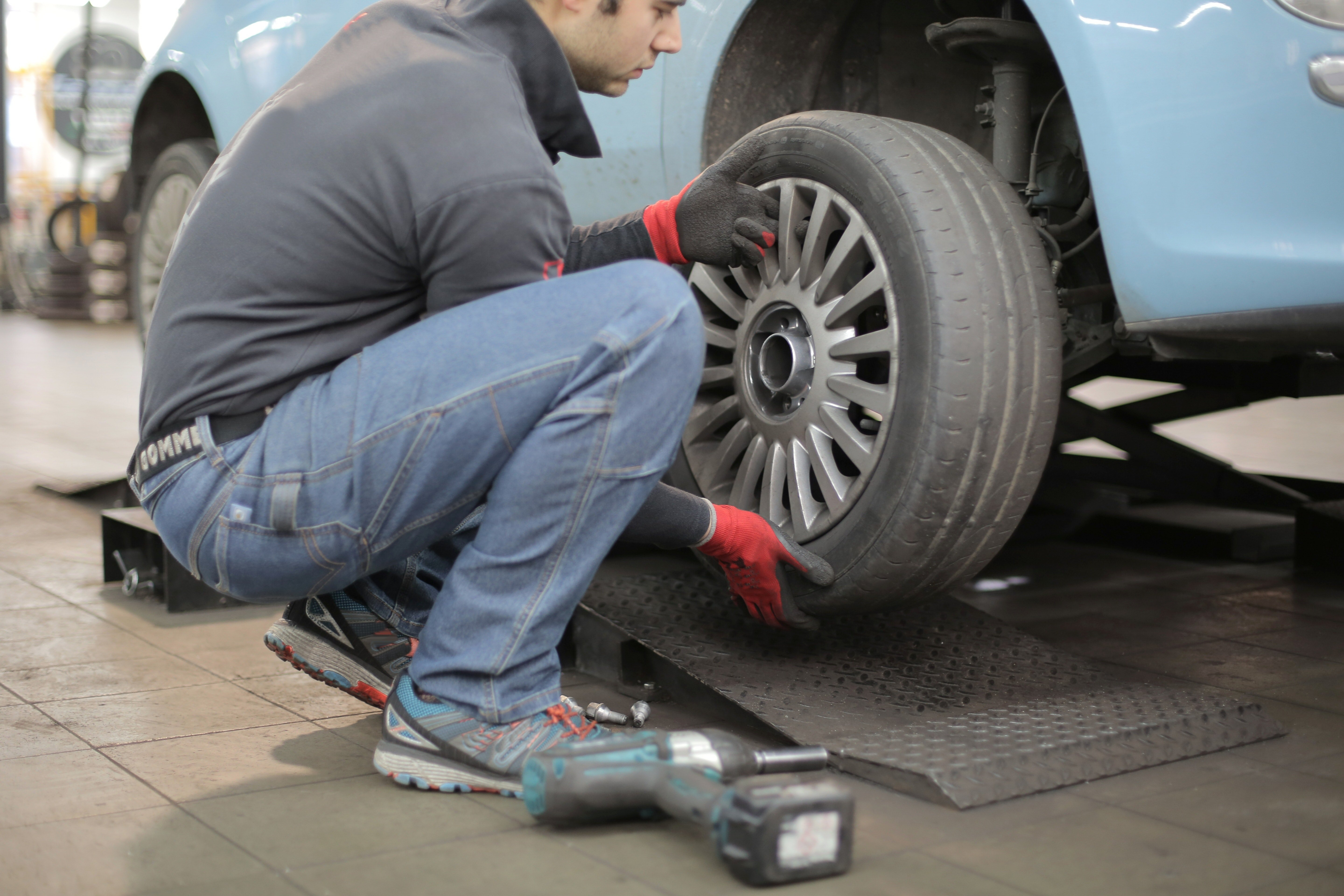 Pictured - A photo of a man changing a tire wearing jeans, a gray jacket and matching gloves | Source: Pexels