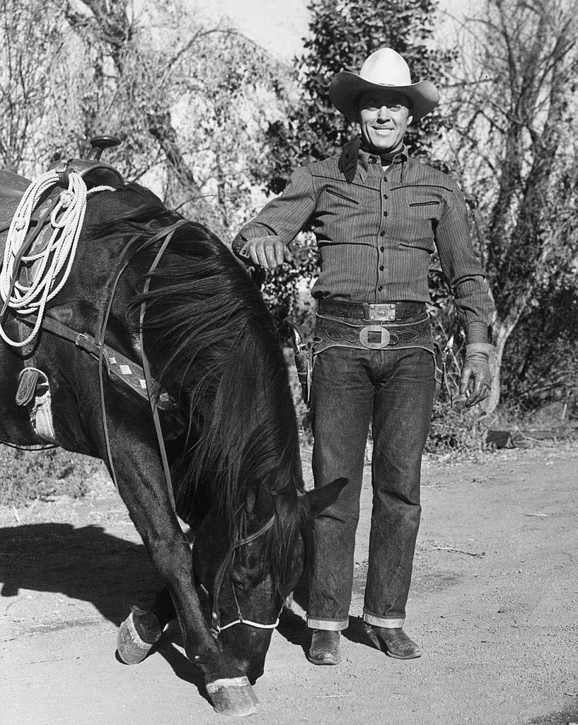 American film actor and former athlete Allan 'Rocky' Lane (1901 - 1973), in costume as a cowboy during a location shoot.