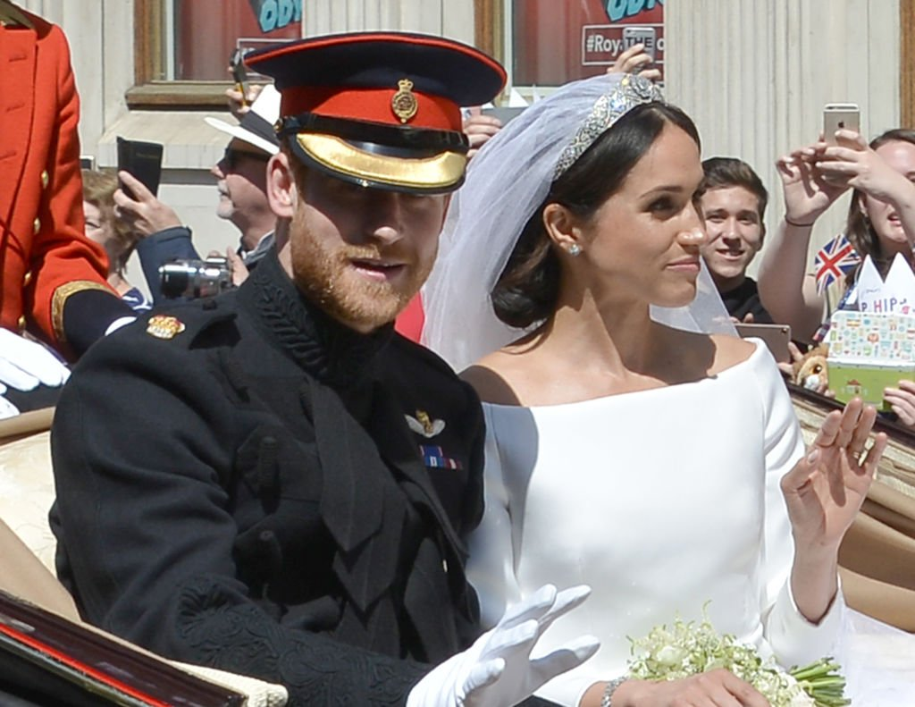 Prince Harry and Meghan Markle riding on a horse carriage on their wedding day with the Duchess of Sussex waving at royal fans on May 19, 2018, in Windsor, England   Photo: Getty Images