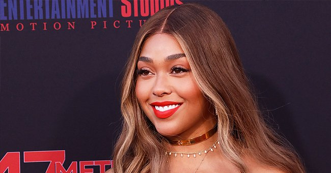 Jordyn Woods Shows off Her Fit Figure Posing in a Silk Green Dress with a Deep Neckline (Photo)