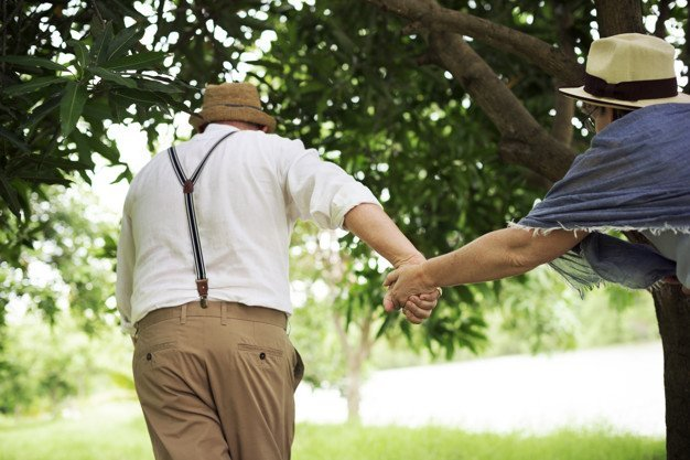Un couple de seniors complices qui court dans un parc | Photo: Freepik