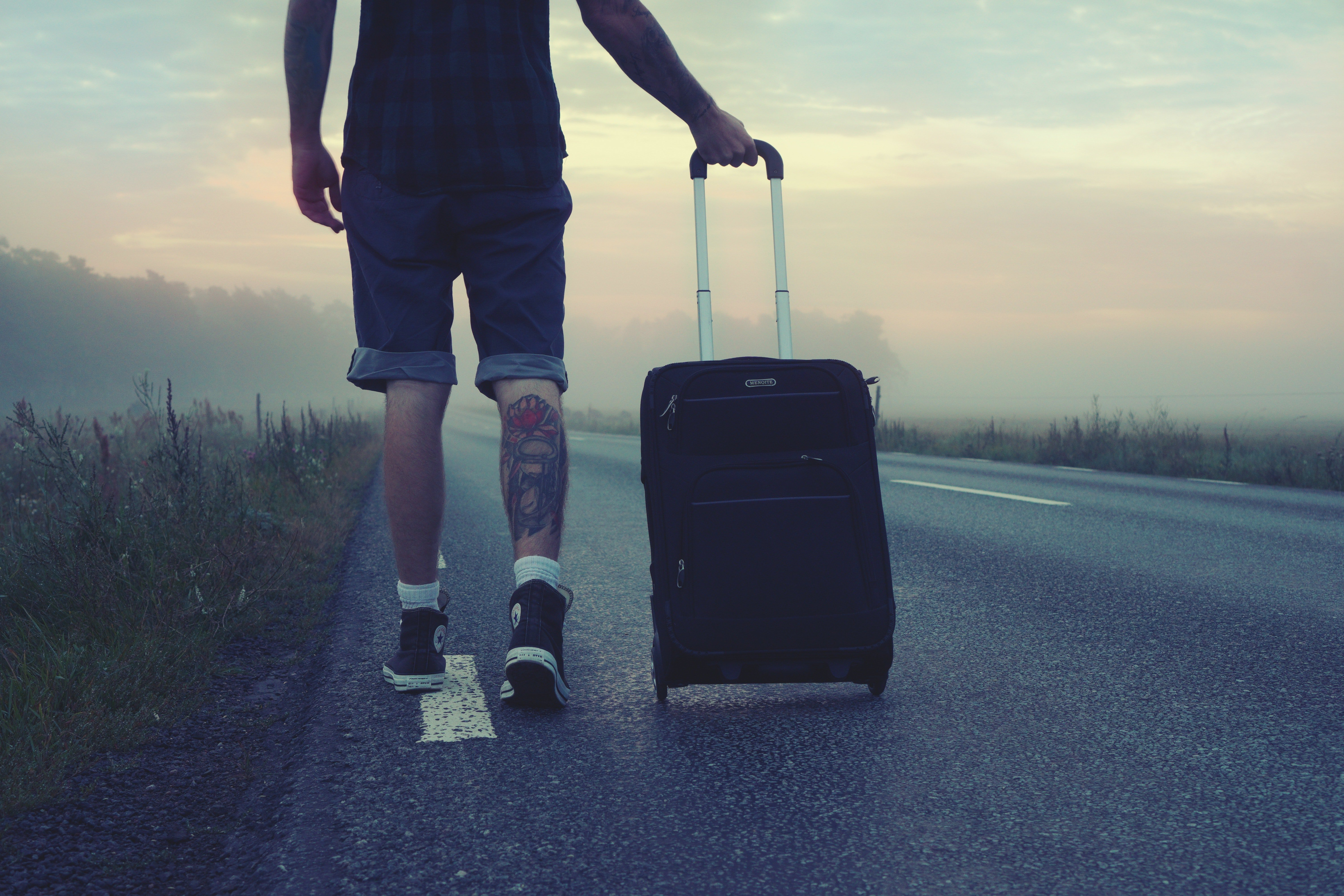 Man walking on an empty road with a black luggage | Photo: Pexels