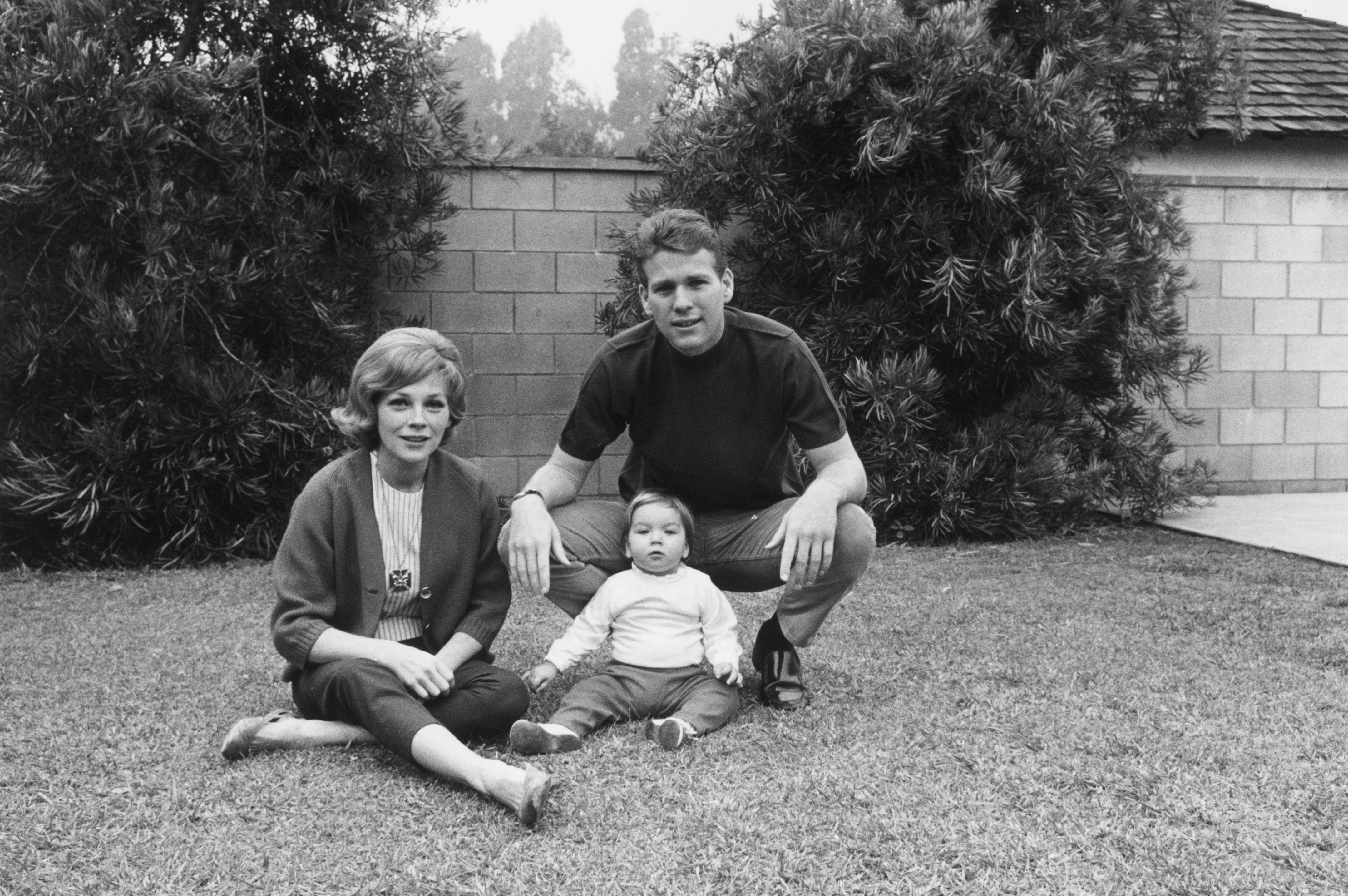 Ryan O'Neal with his wife, actor Joanna Moore, and daughter, Tatum, sitting on grass in front of a stone wall   Photo: Getty Images