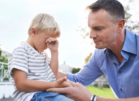 Photo of a father consoling his crying son   Photo: Getty Images