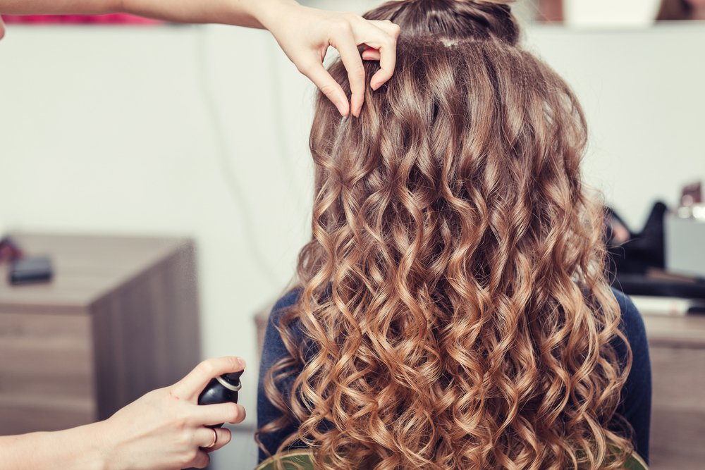 Close-up of hands of a hairdresser at beauty salon, curling female hair with equipment |  Photo: Shutterstock