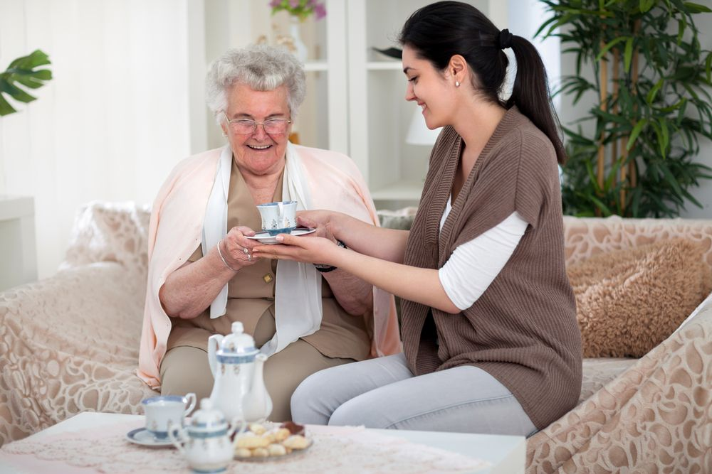 A woman giving an elderly lady a cup of tea. │Source: Shutterstock